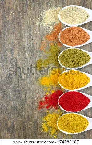 Assorted powder spices in white spoons on wood. Top view point. - stock photo