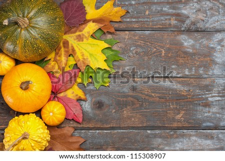 Assorted pumpkins with autumn leaves on wooden table - stock photo