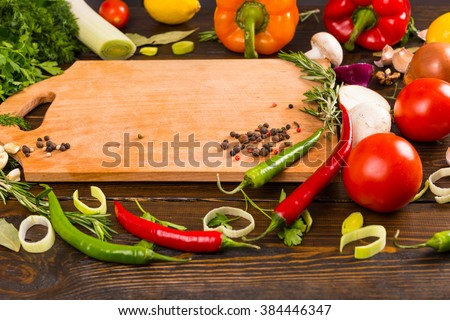 Assorted red and green hot spicy peppers, tomatoes, mushroom and onions surrounding empty wooden cutting board - stock photo