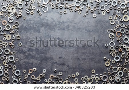 Assorted screw nuts and bolts frame on metal texture background - stock photo