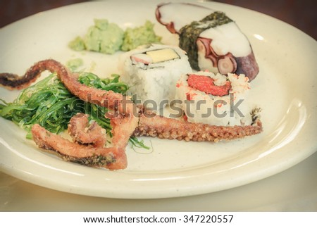 Assorted seafood plate with fried squid legs seaweed salad sushi octopus and wasabi - stock photo
