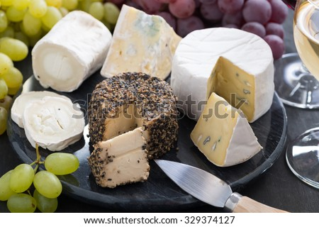assorted soft cheeses and snacks to wine, close-up, horizontal - stock photo