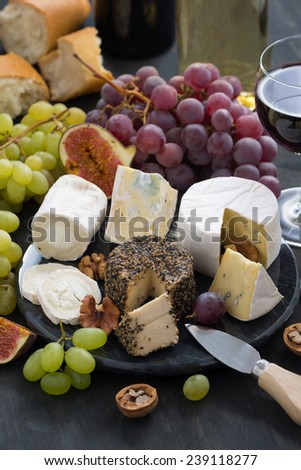 Assorted soft delicacy cheeses and appetizers to wine, top view, vertical, close-up - stock photo