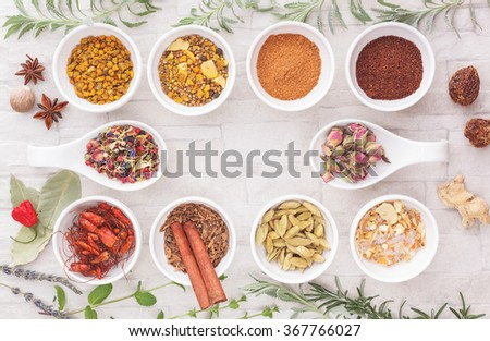 Assorted spices and herbs. An arrangement of spices and herbs on rustic background.  Top view, blank space, vintage toned image. Natural light - stock photo