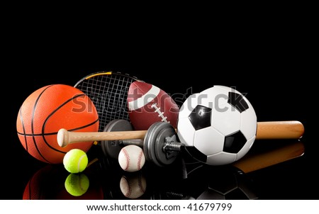 Assorted sports equipment including a basketball, soccer ball, tennis ball, baseball, bat, tennis racket, football and dumbbells on a black background - stock photo