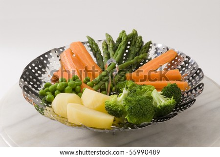 Assorted steamed vegetables in a steamer. White background. - stock photo