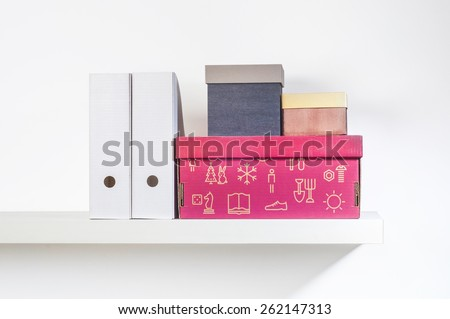 Assorted storage boxes placed on a wall shelf - stock photo