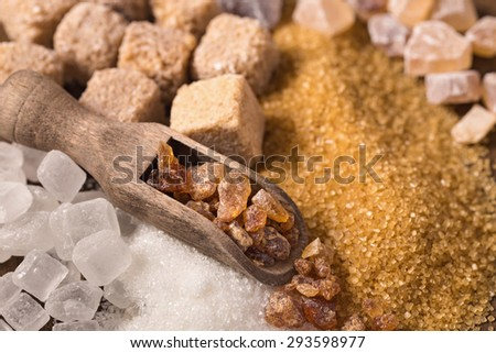 Assorted sugar and wooden scoop closeup - stock photo