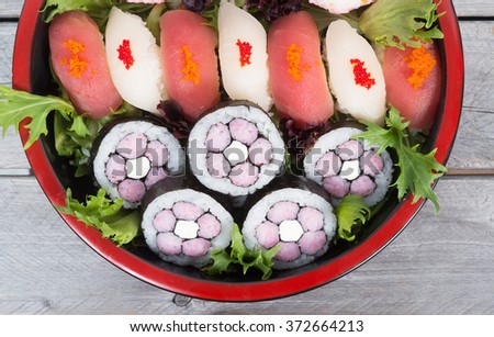 Assorted sushi and maki in a nice tray on wooden table - stock photo