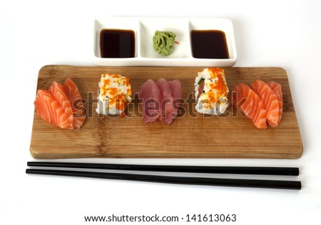 assorted sushi and sashimi on a wooden plate with soy and chopsticks - stock photo