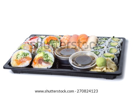 Assorted sushi rolls in a black plastic tray against white background - stock photo