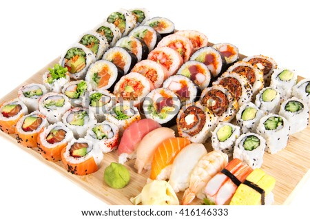 Assorted sushi rolls on a wooden board isolated on white background - stock photo