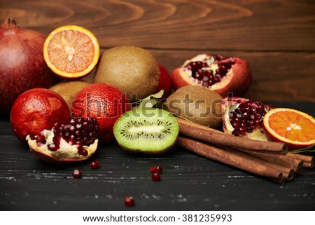 assorted tangerine kiwi apple orange and pomegranate on rustic wooden table with cinnamon sticks. Shallow depth of field - stock photo