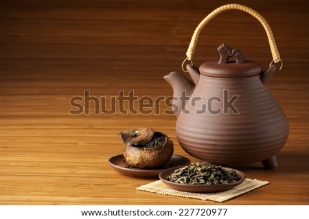 Assorted tea and ceramic teapot on wooden background with copy space. - stock photo