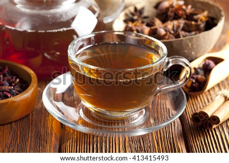 Assorted tea leaves, cup of tea and teapot on wood - stock photo