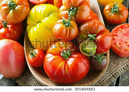 assorted tomatoes on wooden surface - stock photo