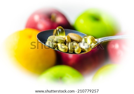 Assorted vitamins and nutritional supplements in serving spoon  consist of drug capsule consists of Vitamin pills,CoQ10 pills,Vitamin C pills,Vitamin B pills,fish oil pills, and multi-vitamin capsule - stock photo