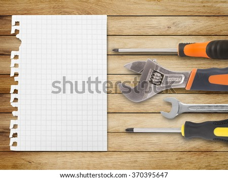 Assorted work tools and notebook paper on wood - stock photo