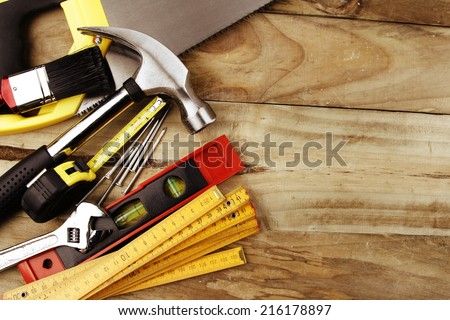 Assorted work tools on wood - stock photo