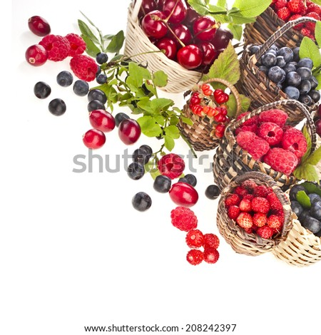 Assortment mix of summer fresh forest berries in the basket isolated on white background - stock photo
