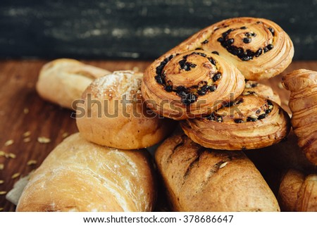 assortment of baked bread, baguette for breakfast on linen napkin on the wood table with black background - stock photo