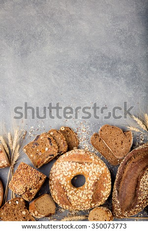 Assortment of baked bread on stone table background Composition with bread slices  and rolls Copy space - stock photo