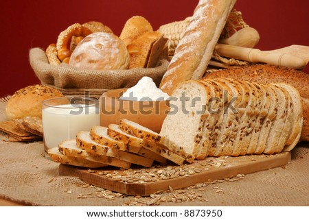 Assortment of baked breads with yogurt and a bowl of flour on red background - stock photo