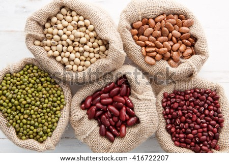 Assortment of beans and lentils in hemp sack on wooden background. green bean, groundnut, soybean, red kidney bean , black bean ,red bean and brown pinto beans - stock photo