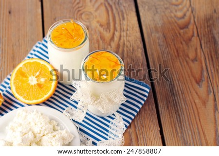 Assortment of breakfast products (homemade yogurt, cottage cheese; orange jam) on a wooden table. Selective focus, copy space background - stock photo