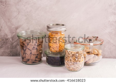 Assortment of cereals, flakes, nuts and berries in storage glass jars over kitchen table. Homemade granola bar ingredients. Toned image - stock photo