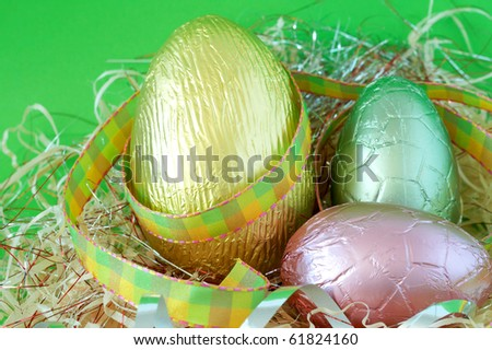 Assortment of chocolate Easter eggs wrapped in straw on green paper background - stock photo