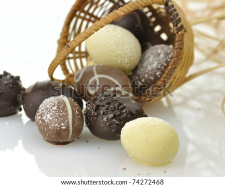 assortment of chocolate eggs and  a basket, close up - stock photo