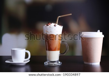 Assortment of coffee drinks on wooden table, on bright background - stock photo