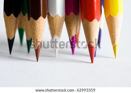 Assortment of colored pencils on white paper - stock photo