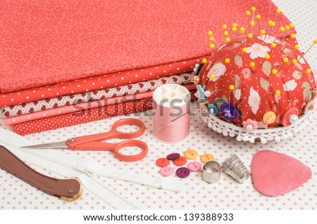 Assortment of colorful fabrics and sewing tools for quilting. - stock photo