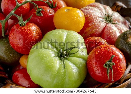 Assortment of colorful heirloom tomatoes with water drops in dark wooden basket - stock photo