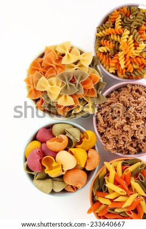 Assortment of colorful pasta in color bowls isolated on white - stock photo