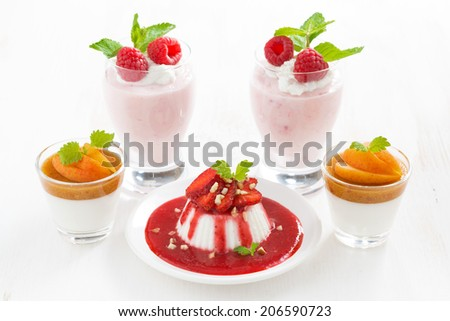 assortment of desserts with cream jelly and fresh berries on white table, horizontal - stock photo