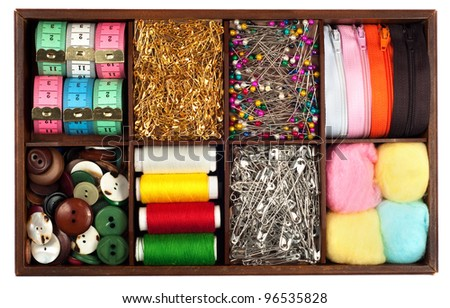 Assortment of different   tailoring materials (tape-measure,safety pins,needles,zippers,buttons,spivels,threads and cotton balls)  arranged in vintage or retro wooden box isolated on white background - stock photo