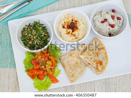 Assortment of dips: hummus, chickpea dip, tabbouleh salad, baba ganoush and flat bread, pita on a plate. Summer outdoor background - stock photo