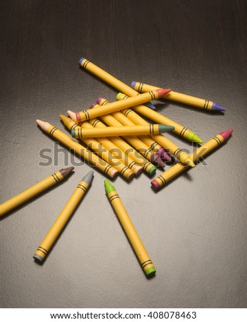 Assortment of drawing tools/Colored Crayons/Various artist pigments on a simple surface - stock photo