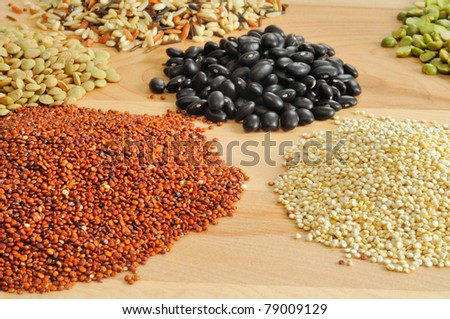 Assortment of dry foods--red and white quinoa, lentils, peas, black beans, and wild rice--on a cutting board - stock photo