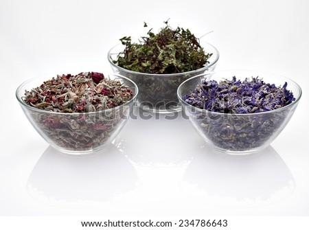 Assortment of dry medicinal herbs in glass bowls (melissa, clitoria, rose, calendula, daisy, sage) - stock photo