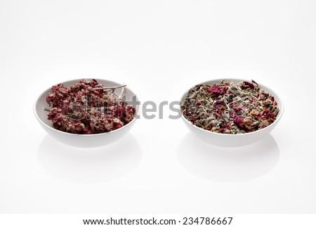 Assortment of dry medicinal herbs in glass bowls (rose, calendula, daisy, antennaria, sage) - stock photo