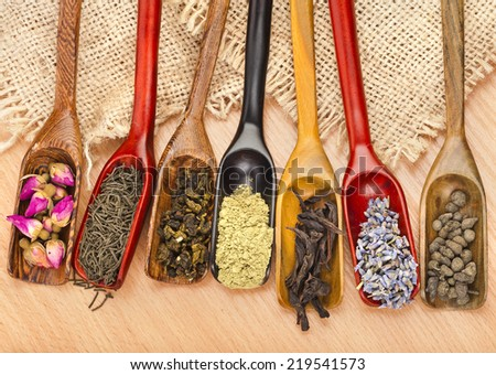assortment of dry tea in scoops on wooden table background, top view - stock photo