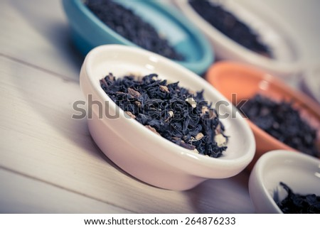 assortment of dry tea in small bowl, on wooden background - stock photo