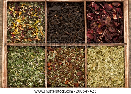 Assortment of dry tea in wooden box - stock photo