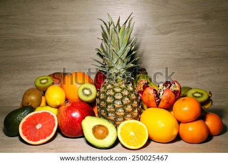 Assortment of exotic fruits on wooden background - stock photo