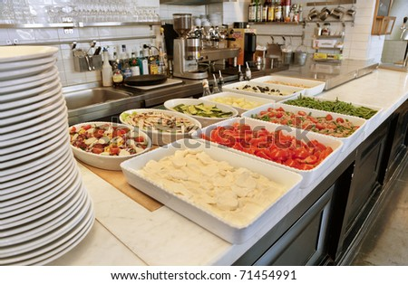 Assortment of food in large trays laid out on a restaurant kitchen counter-top. - stock photo