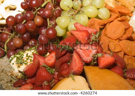 Assortment of fresh and dried fruits with a variety of cheeses - stock photo